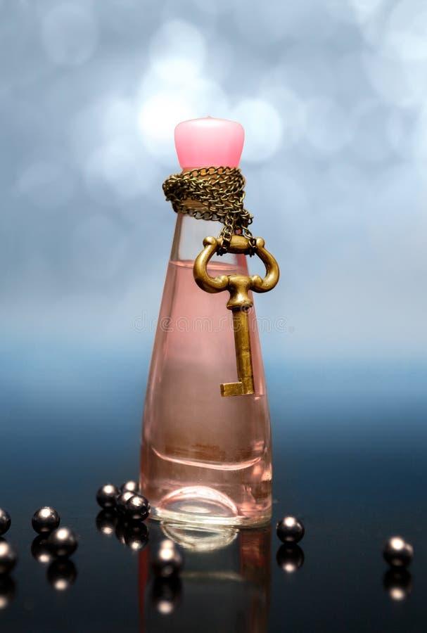 Philtre d'amour séduisant dans une bouteille avec la chaîne et clé autour de photo libre de droits