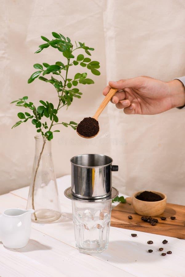 'Phin 'traditionell vietnamesisk kaffebryggare Det första stället på överkanten av exponeringsglas, tillfogar jordningskaffe häll royaltyfria foton