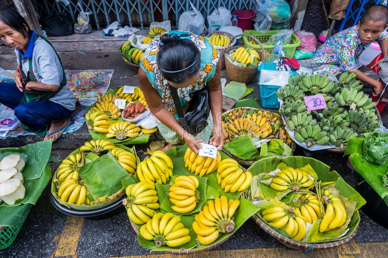 Local woman putting price tag down on her bananas at a local fresh market in Phisanulok, Thailand. Phisanulok, Thailand - 29 July 2017 - Local Thai woman put stock images