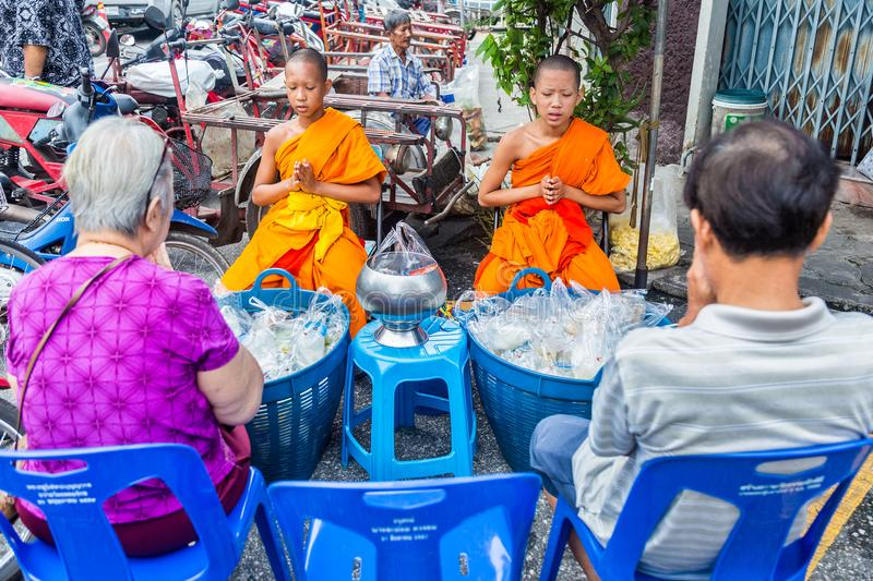 Two young monks chanting in front of two Thai people at a local stock photos
