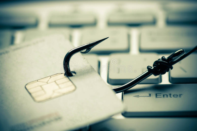Phishing. Credit card phishing attack / credit card with a hook on keyboard royalty free stock photo