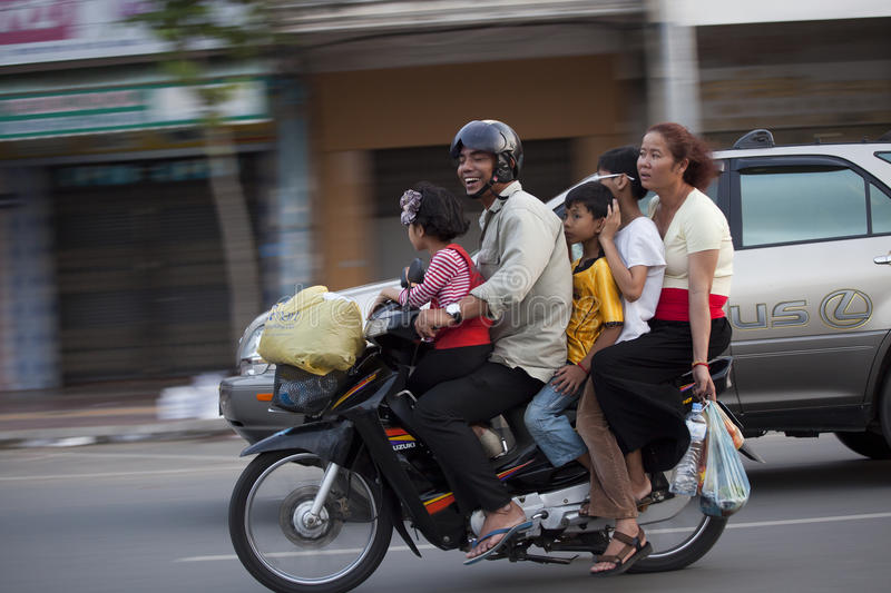 """Family on motorbike in Phnom Penh, Cambodia. Phnom Penh is the capital of Cambodia. Located on the banks of the Mekong Rouge once was known as the """"Pearl royalty free stock photo"""