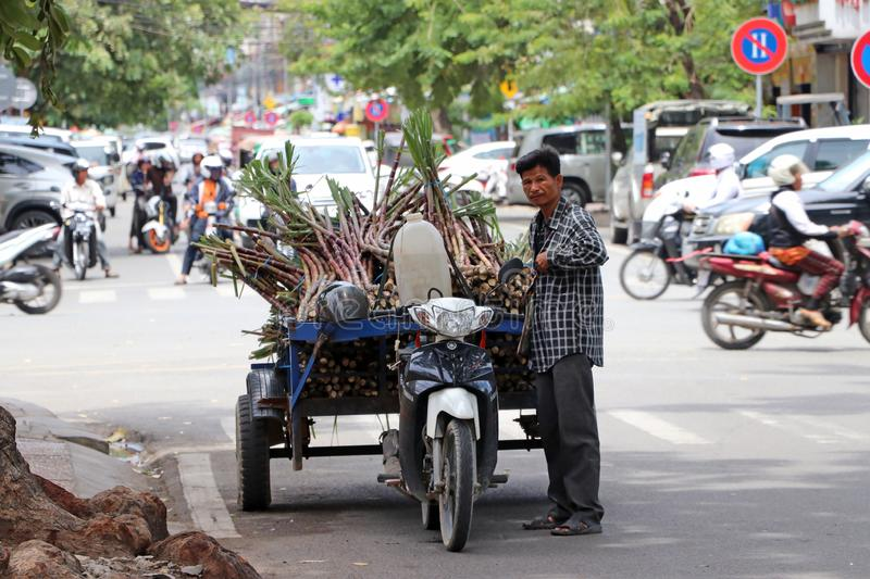 Cambodian man standing with his three wheels motorcycle carrying sugarcane to be delivered on the street stock images