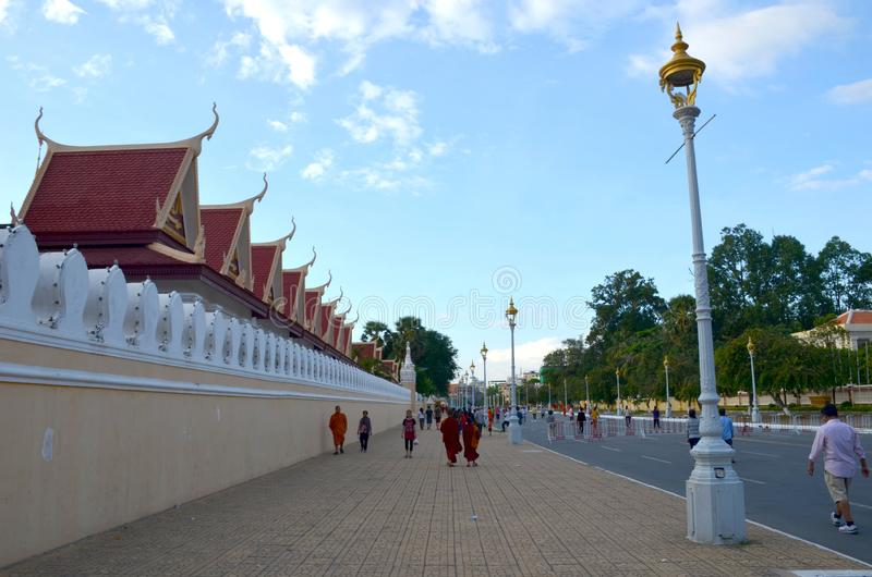 PHNOM PENH, CAMBODIA - December 11, 2015: Monks and locals walk along the street near the walls of the royal palace in Phnom Penh stock image