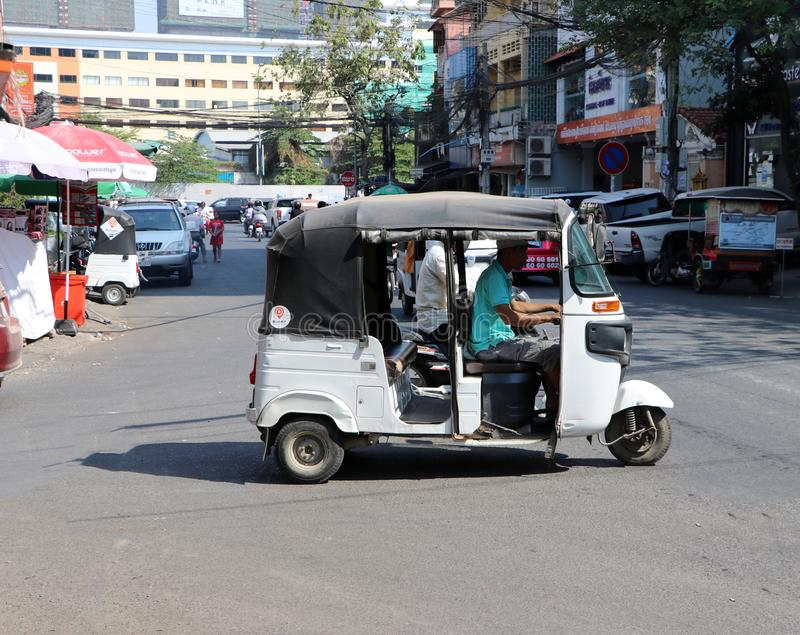 Tuk Tuk or Taxi tricycle on the road, Lifestyle of traffic in Phnom Penh. It is a three-wheeled motorized vehicle used as a taxi stock images