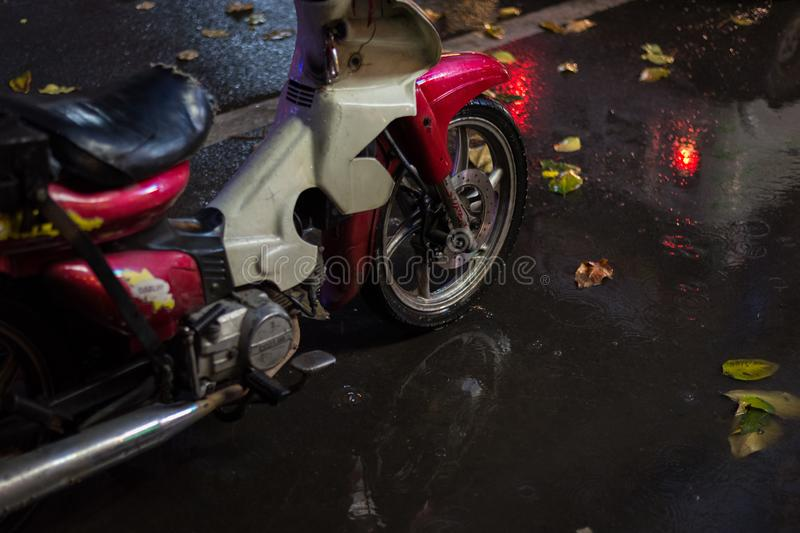 Phnom Penh, Cambodia: a motorbike stands on the night street in the rain, in the puddle with wet fallen leaves stock photos