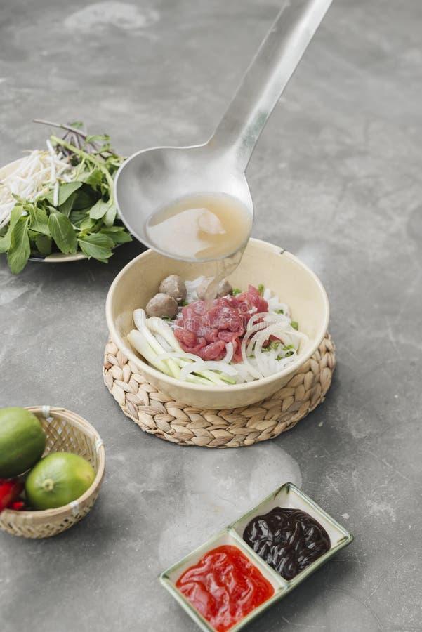 Pho BO - Sopa de macarronete fresca vietnamiana do arroz com carne, ervas e pimentão Conservado em estoque que está sendo derrama imagens de stock royalty free