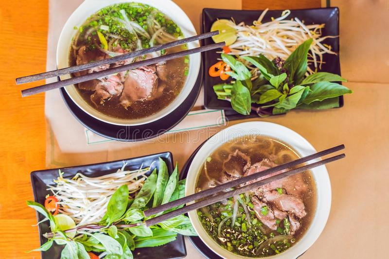 Pho Bo - Vietnamese fresh rice noodle soup with beef, herbs and stock photos