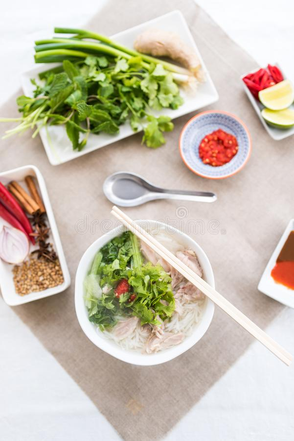 Pho ga soup with the serving sauces, herbs and spices royalty free stock photo