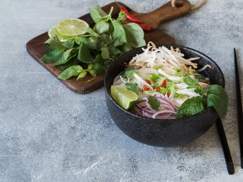 Pho vietnamien traditionnel GA de soupe dans la cuvette noire avec les nouilles de poulet et de riz, la menthe et l'oignon de cil photos stock