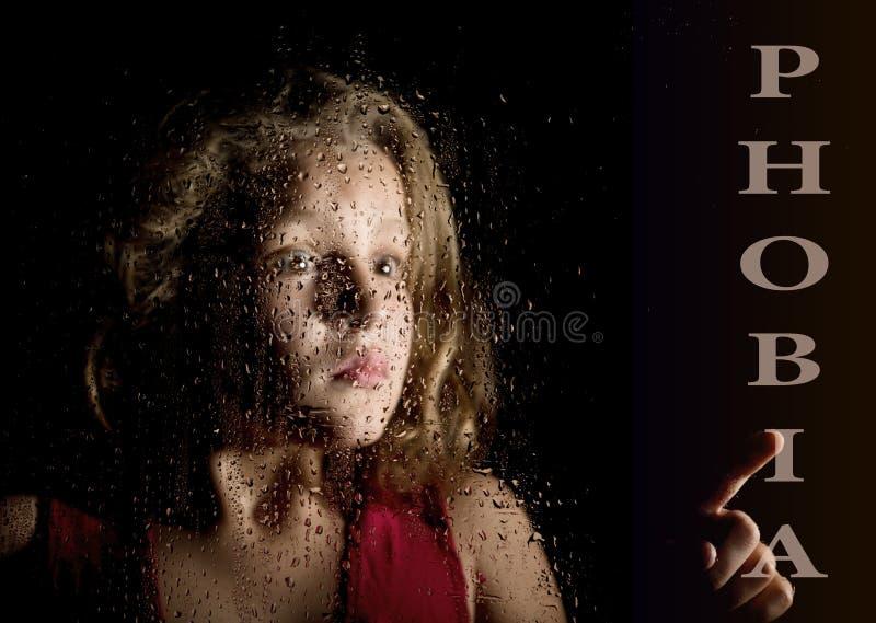 Phobie écrite sur l'écran virtuel main de la mélancolie effrayée de jeune fille et triste à la fenêtre sous la pluie photos libres de droits