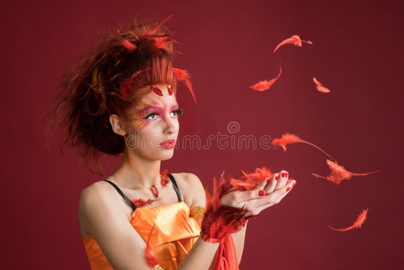 phoenix Penas do retrato e do voo da moça A mulher guarda uma pena nas mãos fotos de stock royalty free