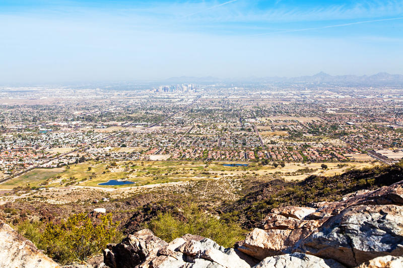 Phoenix Skyline View From South Mountain Hiking Trail. View from Dobbin's Point on South Mountain in Phoenix, Arizona with rocks in foreground and cityscape in royalty free stock photo