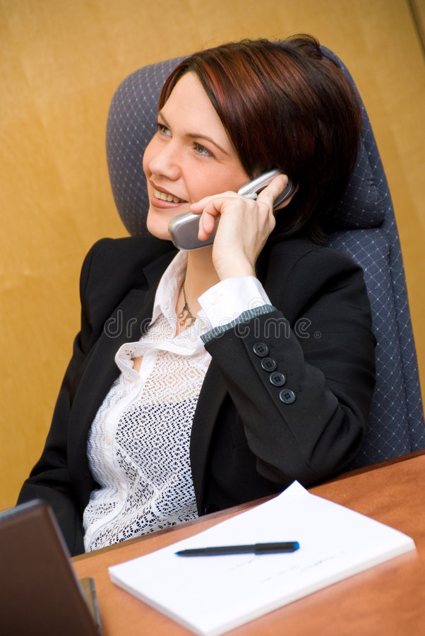 On the phone. Cute business woman on the phone chatting stock photo
