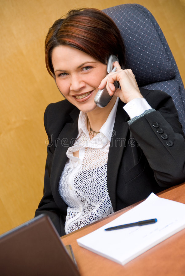 On the phone. Cute business woman on the phone chatting royalty free stock photo