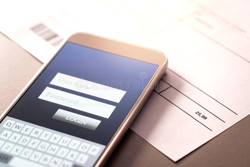 Phone bill and smartphone with online bank app. royalty free stock image