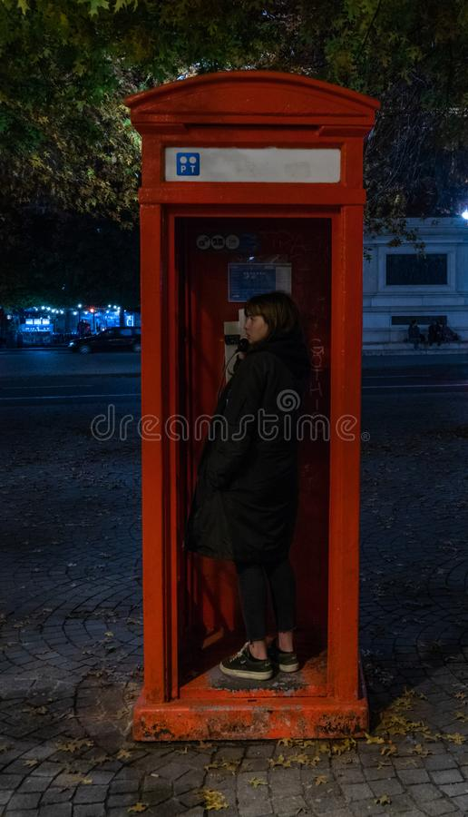 Phone box with a girl typicall english. Style royalty free stock photo