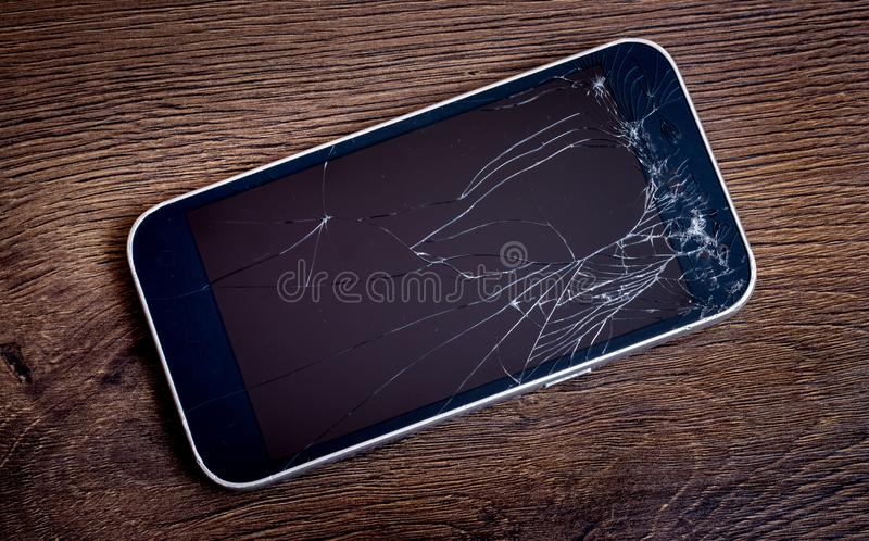 Phone with broken glass on a dark wooden background_. Phone with broken glass on a dark wooden background royalty free stock images