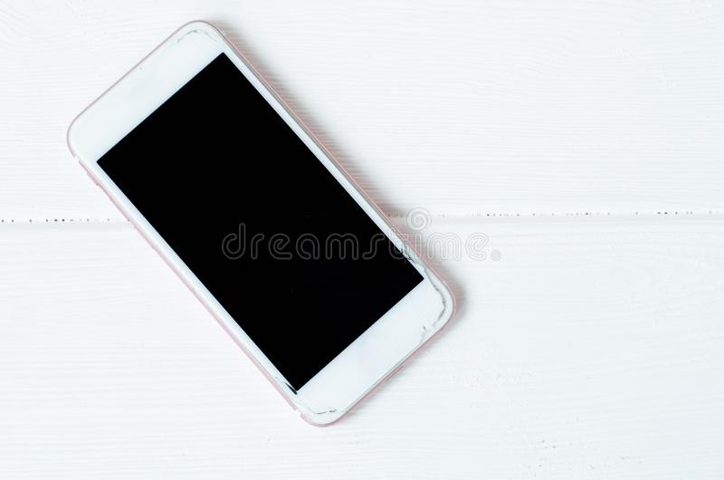 Phone with broken screen on white wooden background. Top view. Concept of repairing royalty free stock photos