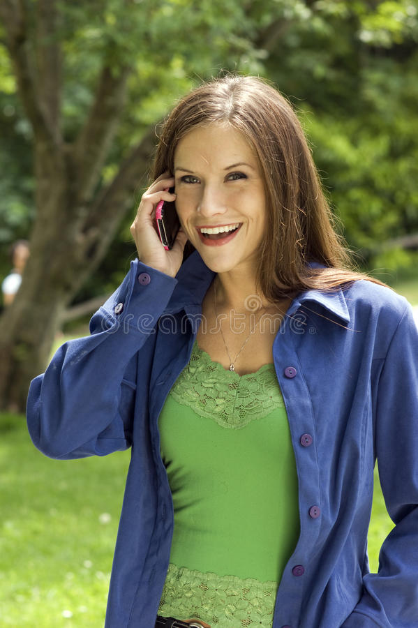Woman Takes Cell Phone Call in the Park stock photos