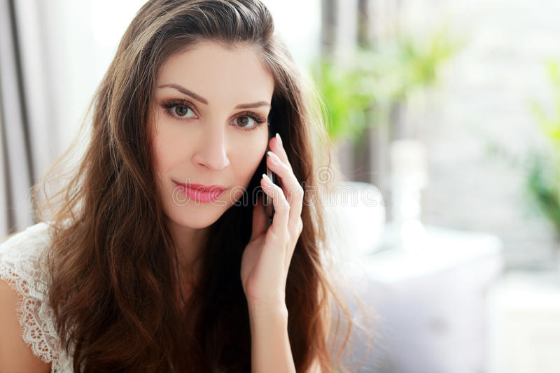 Phone call at home. Smiling brunette sitting on her couch on a phone call at home in the living room stock photos