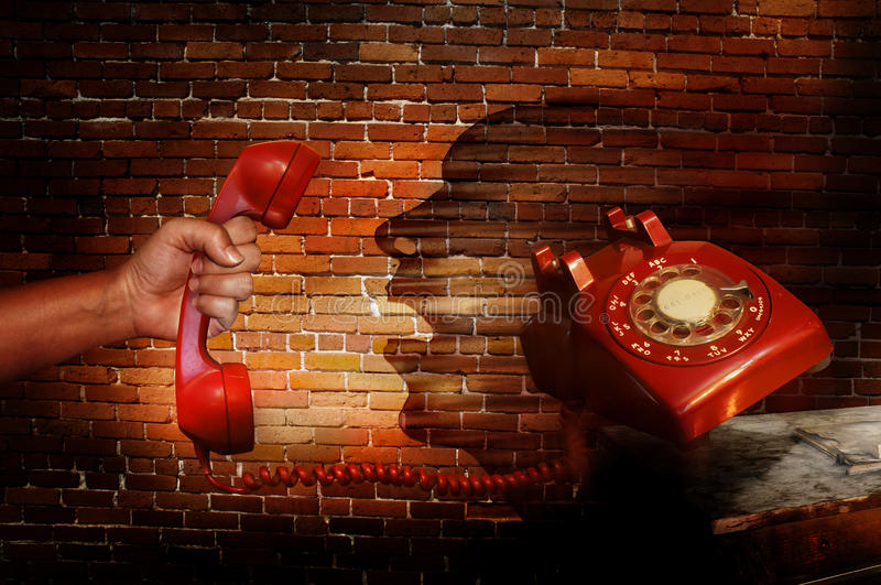 Phone call. A red telephone with dial begin held by a clenched fist. The phone is falling off of a table and graffiti on the wall depicts a person yelling into royalty free stock images