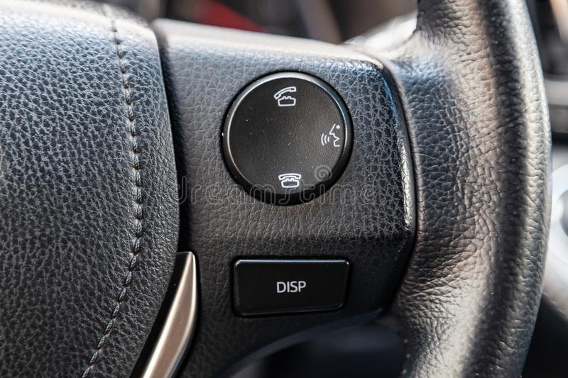 Phone control buttons via bluetooth on the steering wheel of a car close-up, the system royalty free stock image