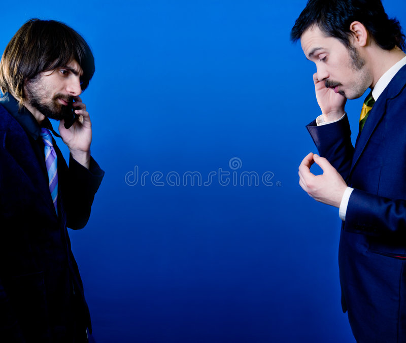 Phone conversation. Two young businessmen standing opposite each other, talking on their mobile phones separately royalty free stock photography