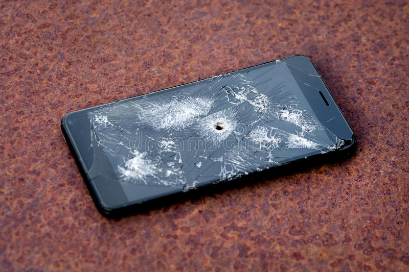 A phone with cracks and a hole from a bulletagainst a background of rusty metal. Consequences of shooting_ stock image