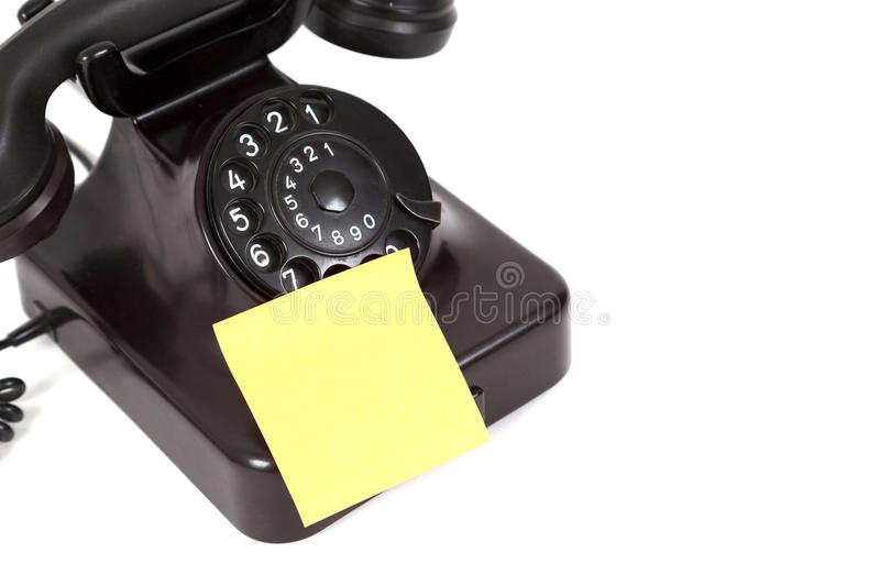 Phone and empty note on it. Concept made of old rotary phone and note on it royalty free stock photography