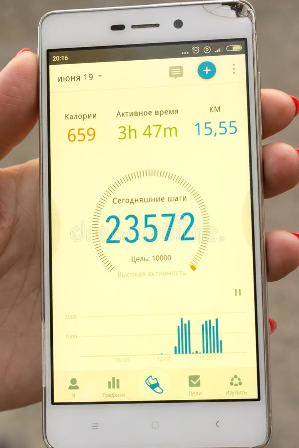 Phone with fitness application in the hand of a woman stock images