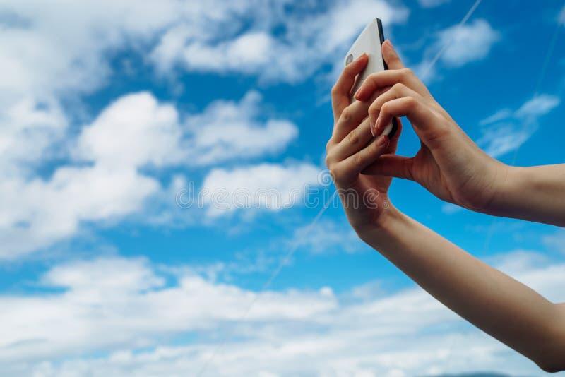 Phone in hand on blue sky stock photos