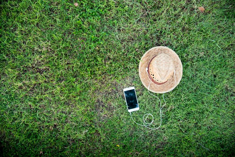 Phone with headphone on green grass with straw hat royalty free stock photos