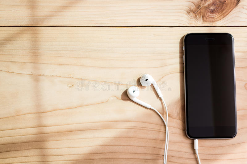 Phone and headphone on wood. Background royalty free stock photos