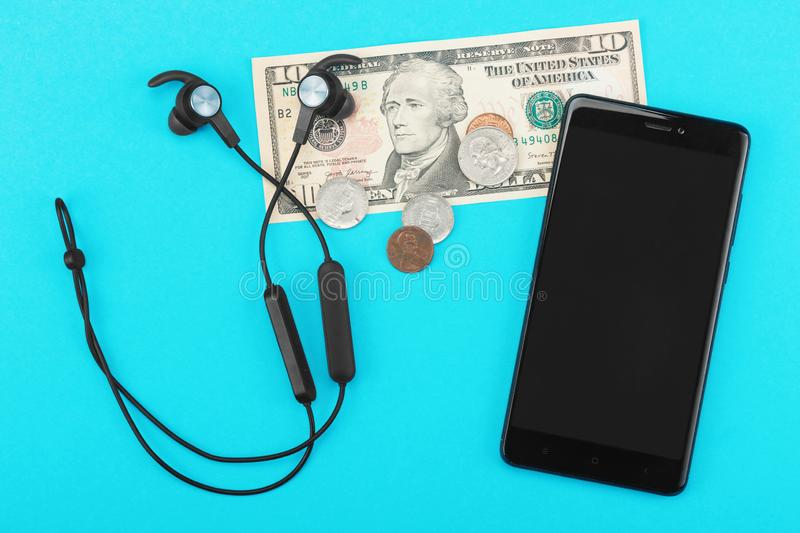 Phone, headphones and pocket money on a blue background stock images