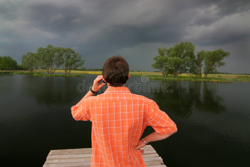 Phone at the lake. A boy is phoning at the lake stock image