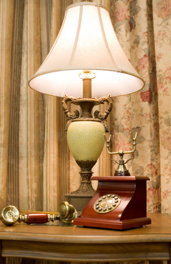 Phone and lamp. Antique phone hang up near lamp stock image