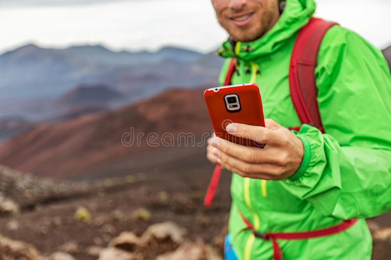 Phone man texting during trek hike in volcano mountain. Young person on travel lifestyle using his smartphone royalty free stock image