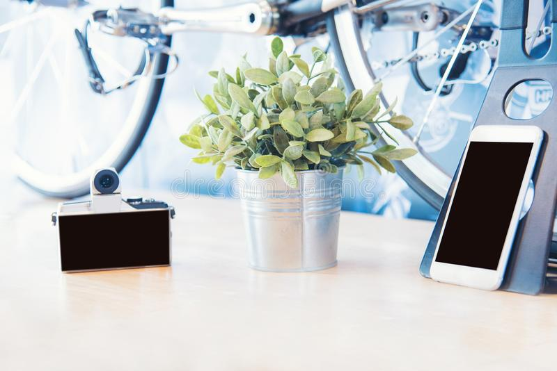 Phone mobile mirrorless digital camera and bicycle new technology for urban city lifestyle. Object on wooden table stock photos