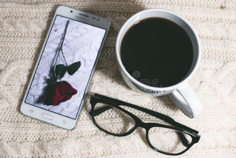 Phone Near Mug and Eyeglasses on Table royalty free stock photo