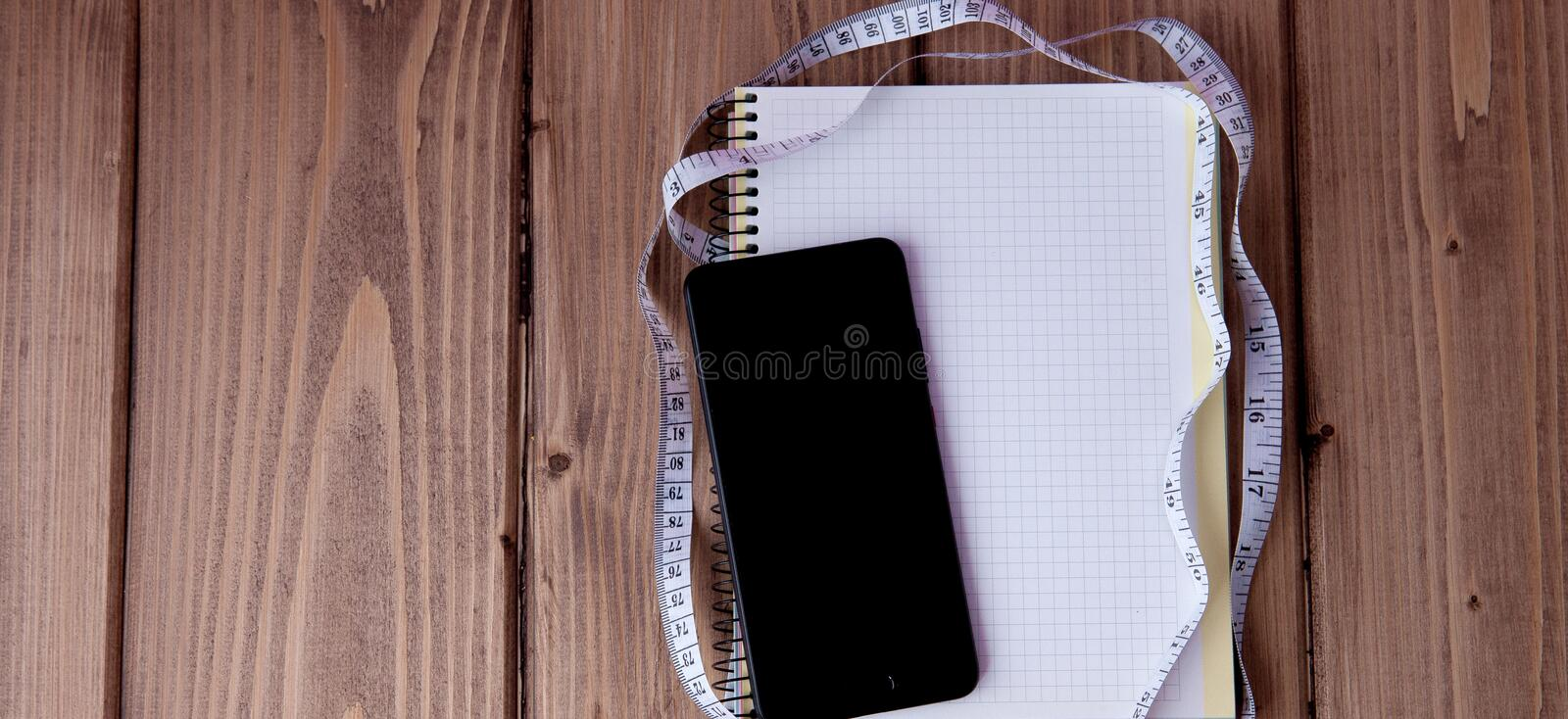 Phone and notebook and meter on a wooden background. Goals for the new year. Planning and schedule concept. To do list.  royalty free stock images