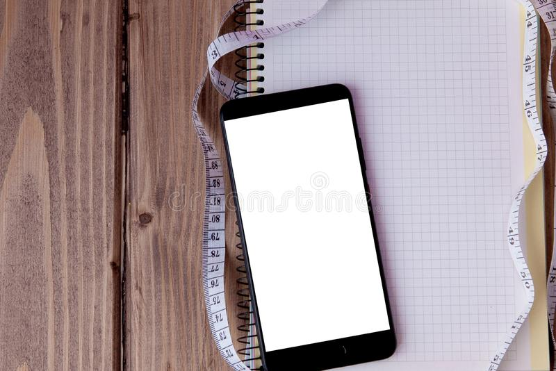 Phone and notebook and meter on a wooden background. Goals for the new year. Planning and schedule concept. To do list.  stock images
