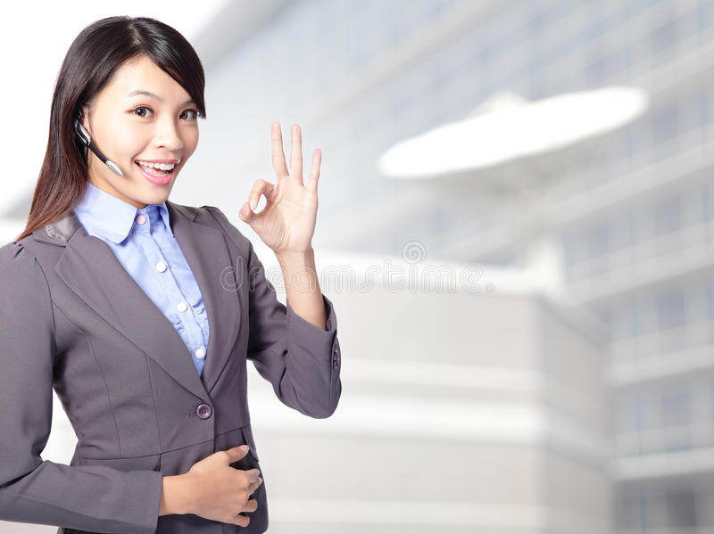 Phone operator in headset showing okay. Portrait of happy smiling cheerful female customer support phone operator in headset showing okay gesture at office royalty free stock image