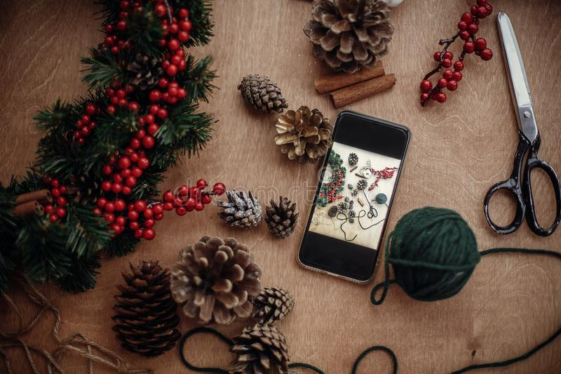 Phone with photo of rustic christmas wreath flat lay. Process of. Making christmas wreath at holiday workshop with fir branches,red berries, pine cones,thread stock photography