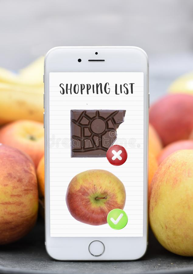 Phone with shopping list healthy vs unhealthy chocolat apple diet stock image
