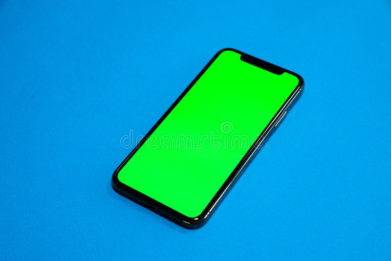 Phone XS, Phone smartphone, green screen on Blue background stock image