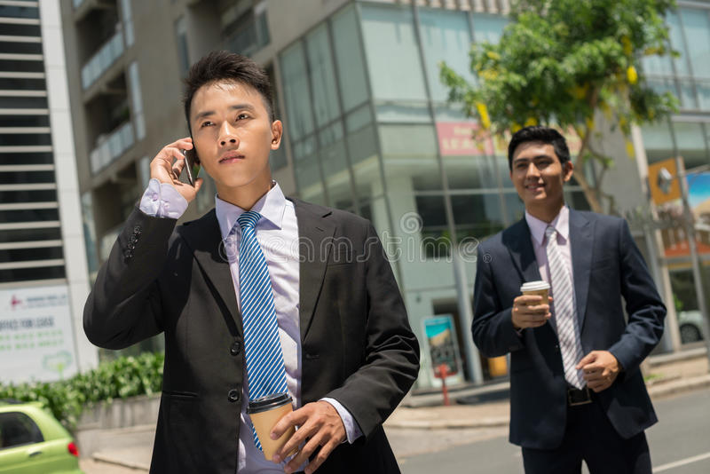 Phone talk. Serious businessman talking on the phone while his colleague waiting for him royalty free stock images