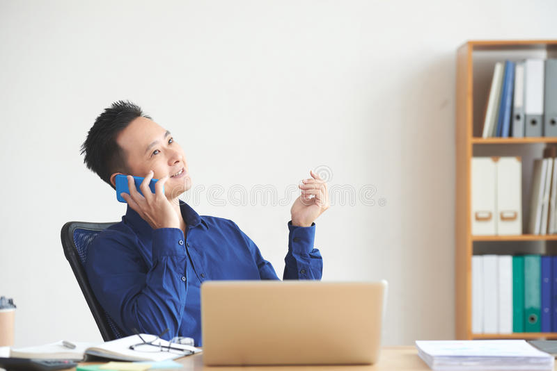 Phone talki. Smiling Asian businessman calling on the phone to his coworker royalty free stock images