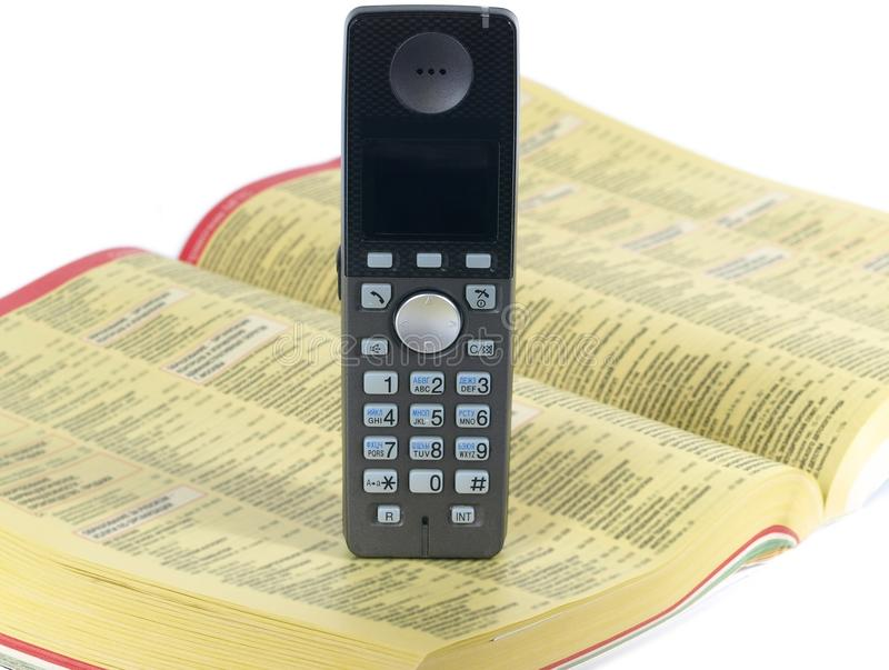 Phone and telephone directory. Cordless phone on the telephone directory royalty free stock photo