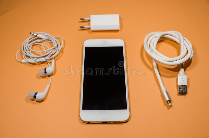 A phone with usb cable and headphones royalty free stock photography